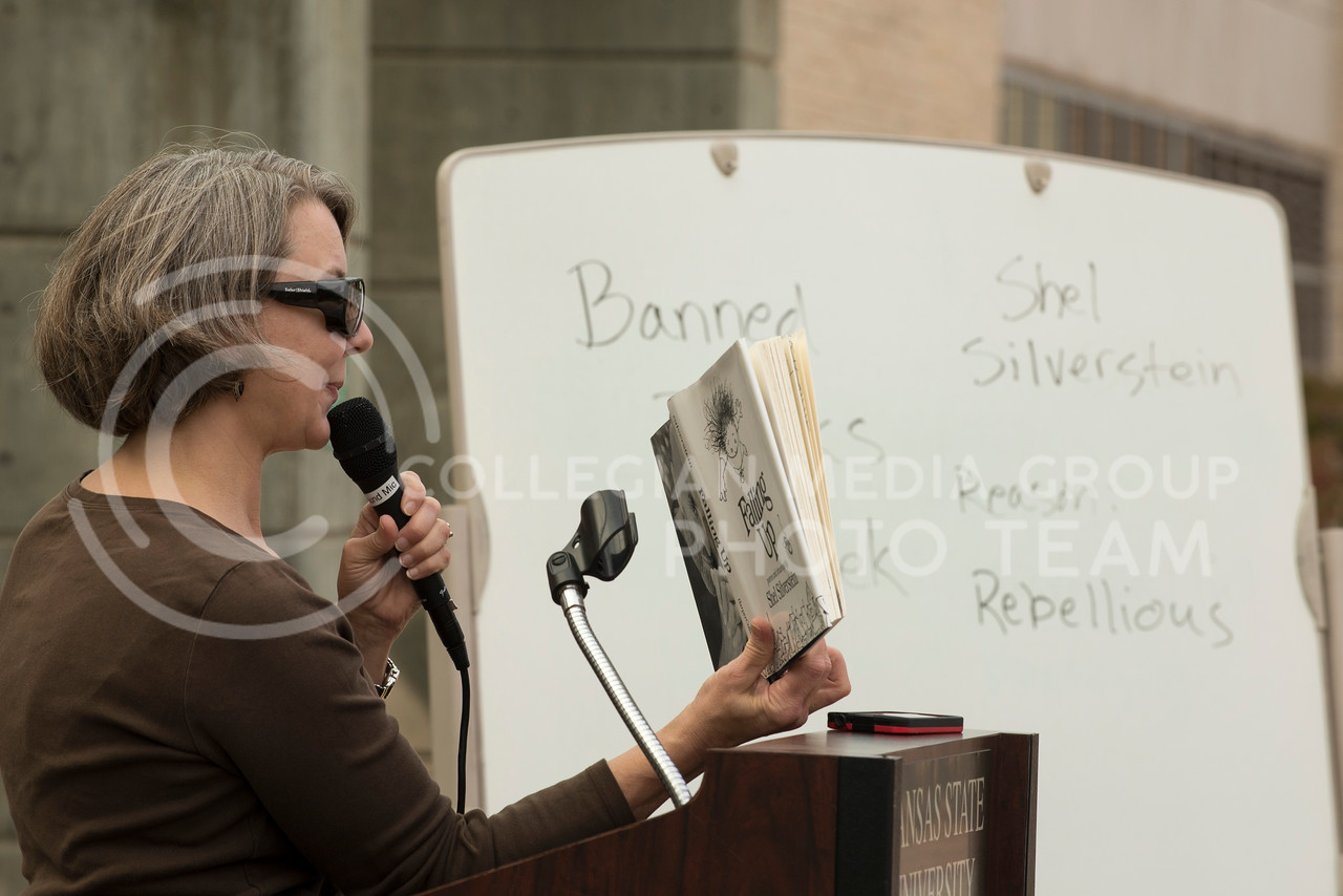 "Naomi Wood, English professor, shows illustrations from Shel Silverstein's book of poems and drawings ""Falling Up"" during the banned book redin gin Bosco Plaza on Wednesday morning, Sept. 24, 2014. Silverstein's book was included in the event because some people believe the book teaches children to be rebellious and disrespectful.  (Hannah Hunsinger 