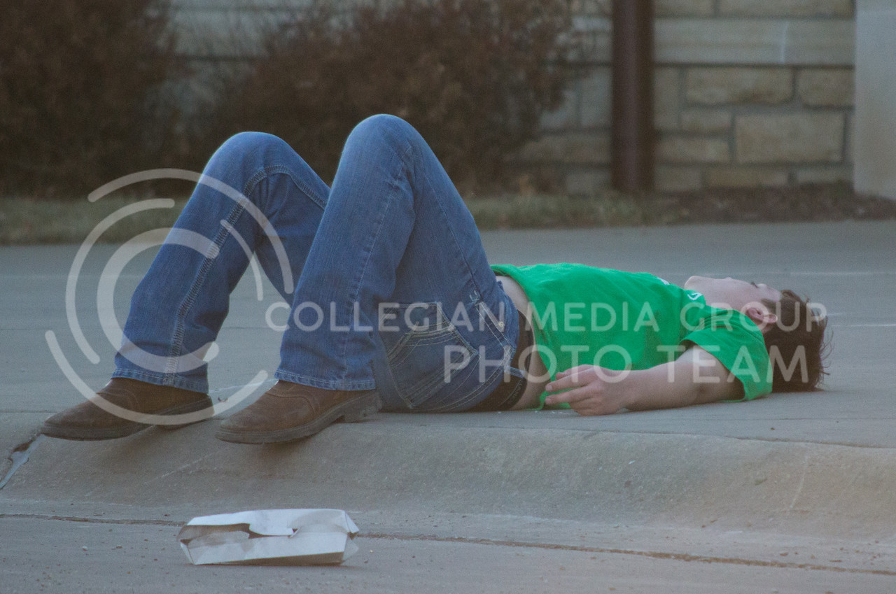 A Fake Patty's Day goer takes a break during the festivities at Fake Patty's Day celebration in Aggieville on Mar. 7, 2015. (Cassandra Nguyen | The Collegian)