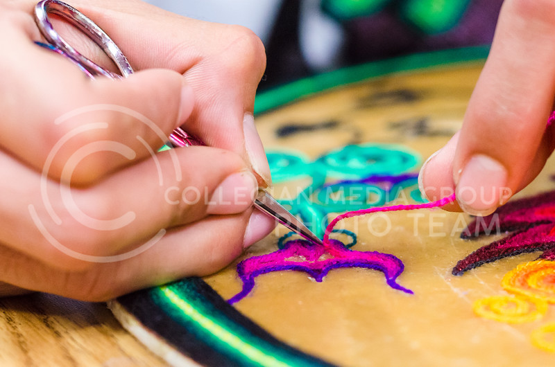 Cilau Valadez makes his Huichol yarn paintings by adhesing yarn to a base coated with beeswax mixed with other natural adhesives during the College of Education's Mexican Art workshop February 17, 2015, in Bluemont Hall. (Parker Robb | The Collegian)