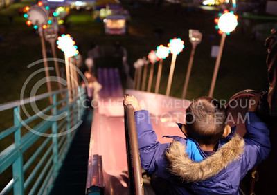 Nichloas, 3, gets ready to slide down next to his father the evening of Oct. 3. at the carnival at Fort Riley (Vail Moshiri | The Collegian)