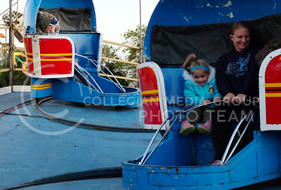 Lynzee Wyatt (blue jacket) enjoys the ride with sister Lea and neighbor Jenn Hurley the evening of Oct. 3. at the carnival in Fort Riley (Vail Moshiri | The Collegian)