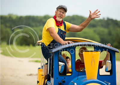 Mardi Gras mini train conductor Ron Lortscher tells his passangers to wave goodbye to their loved ones at the Bayou GatorCraw Fest at Tuttle Creek State Park on July 18, 2015. (Emily Starkey | The Collegian)