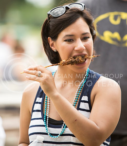 Alyssa Harris of Junction City takes her first bite of alligator at the Bayou GatorCraw Fest at Tuttle Creek State Park on July 18, 2015. (Emily Starkey | The Collegian)