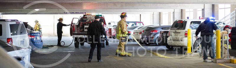 Firefighters unravel a hose to put out a car fire in the K-State parking garage on Feb. 26, 2015. (George Walker | The Collegian)
