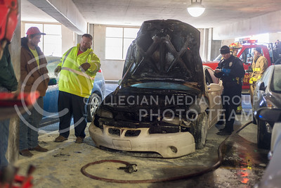 K-State Police, Manhattan Fire Department and Mikes Towing evaluate a car that caught fire inside the second level of the parking garage on campus Feb. 26, 2015. When taken, the owner of the car had not been notified. (Evert Nelson | The Collegian)
