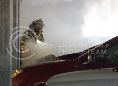 A firefighter works to put out a car fire in the K-State parking garage on Feb. 26, 2015. (George Walker | The Collegian)
