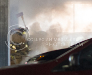Firefighters axe through the hood of a car to put out a fire in the K-State parking garage on Feb. 26, 2015. (George Walker | The Collegian)