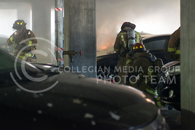 Firefighters work to put out a fire in the K-State parking garage on Feb. 26, 2015. (George Walker | The Collegian)