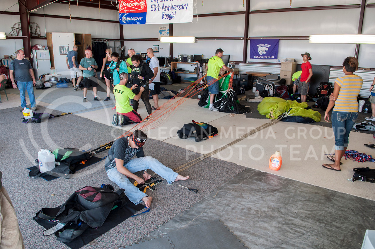 Volunteers repack parachutes for the next round of jumps, while instructors gear up tandem jumpers in a hanger at the Abilene Municiap Airport on Friday morning, Sept. 26, 2014. The K-State Parachute Club celebrated their 50th anniversary over the weekend, offering solo and tandem jumps to alumni, the general public, and skydive enthusists. (Hannah Hunsinger | The Collegian)