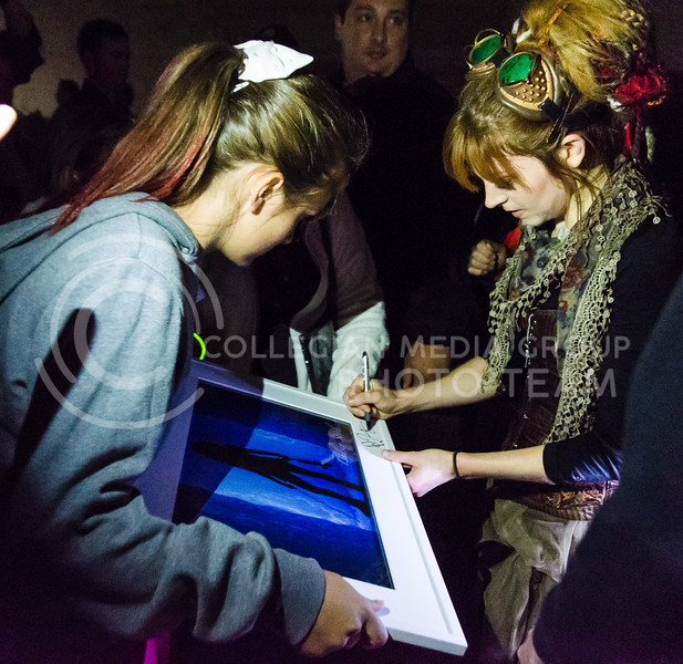 Parker Robb | The Collegian<br /> <br /> Dubstep violinist Lindsey Stirling signs a fan's framed print following her performance on Bosco Plaza September 13, 2014.