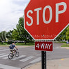 A cyclist runs a stop sign in front of a long line of cars to the left at the intersection of Mid-Campus Drive and Claflin Road Wednesday afternoon. Both drivers and cyclists need to know the rules of the road in order to keep everyone safe and to better integrate with eachother. (Parker Robb | The Collegian)
