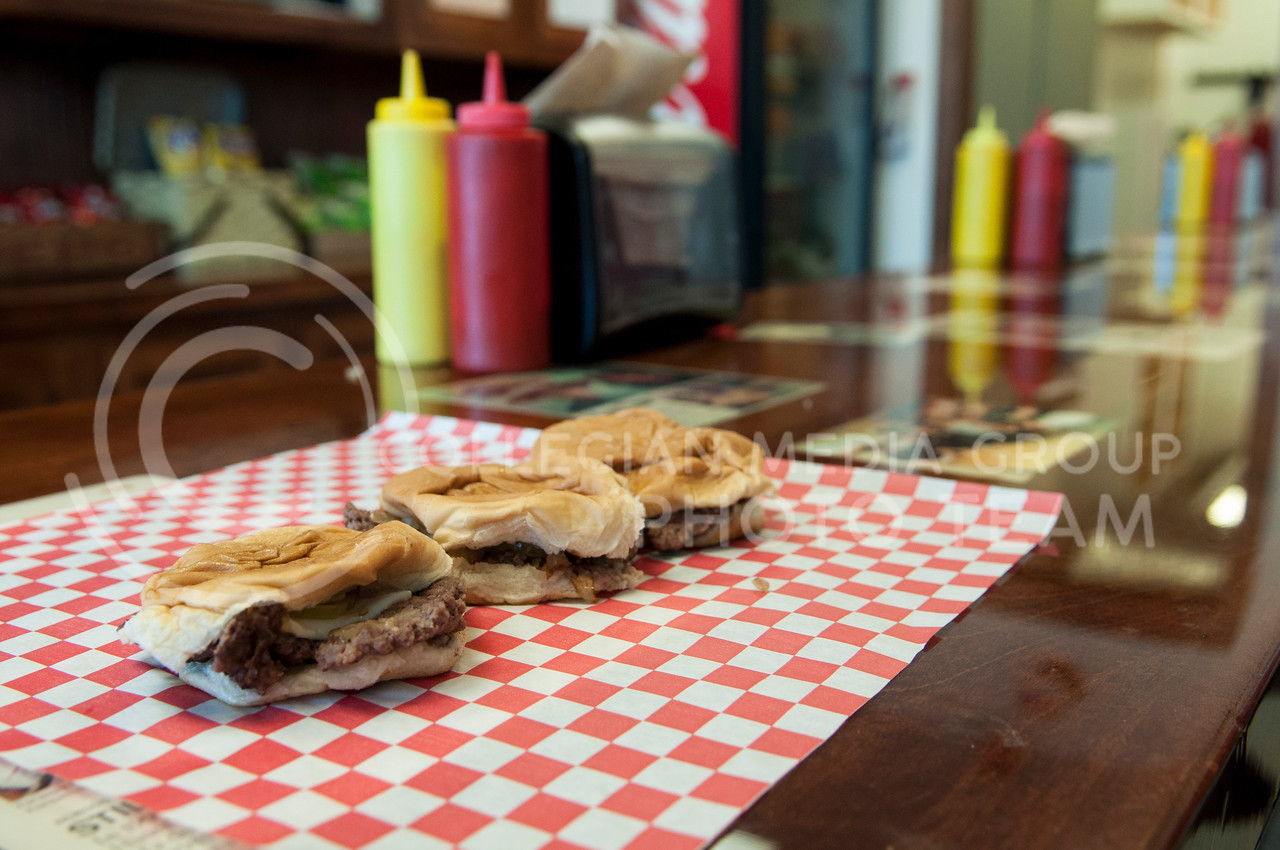 Three Cozy Inn burgers on the counter of the restaurant on Wednesday afternoon, Sept. 17, 2014.  The original Cozy Inn opened in Salina in the 1920s, the Manhattan branch opened in Aggieville about three years ago.  Manhattan's menu differs only slightly from the original's, offering cheese on the burgers, as well as fries and a grinder sandwich.  (Hannah Hunsinger | The Collegian)