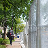 A person walks along the fence erected on the East side of 17th Street next to Meyers Hall May 7, 2015. (Parker Robb | The Collegian)