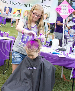 (Photo by Alexander Shaw   The Collegian)  Jessica Sivertsen sprays Eliazabeth Darrah's hair with purple hairspray at Purple Power Play in the Park on Aug. 28, 2014.
