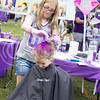 (Photo by Alexander Shaw | The Collegian)<br /> <br /> Jessica Sivertsen sprays Eliazabeth Darrah's hair with purple hairspray at Purple Power Play in the Park on Aug. 28, 2014.