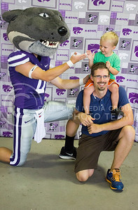 (Photo by Alexander Shaw | The Collegian)   Lucas Shivevs and his son James pose with Willie the Wildcat while James gives Willie a high five at Purple Power Play in the Park on Aug. 28, 2014.