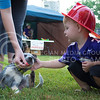 Photo by George Walker | The Collegian<br /> <br /> Rowan Minton, 2 year old Manhatan Resident, pets a blue heeler at Purple Power Play in Manhattan City Park on Aug. 26, 2014. The Manhattan Fire Department gave out plastic fire hats to many people who attended.