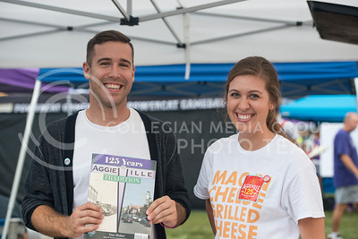 Blair Kocher, 2012 K-State graduate and Hannah Henning, 2014 K-State graduate inform Purple Power Play visitors about AggieVille's 125th anniversary which is September 20, 2014.  Kocher and Henning are members of the AggieVille 125 Committe.