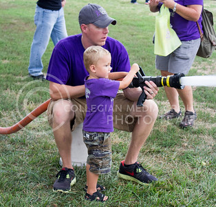 (Photo by Alexander Shaw | The Collegian)   Dillion McDiffett, 3 gets to spray a firehose with Manhattan Fire Department firefighter, Cole Minton at Purple Power Play in the Park on Aug. 28, 2014.