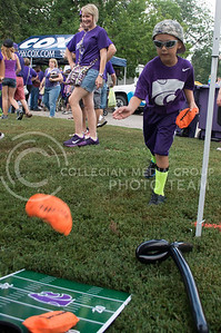 Photo by George Walker | The Collegian  Trewman Haub, 7-year-old Manhattan resident, tosses a football attempting to win a powercat tattoo at Purple Power Play in Manhattan.