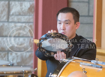 """Alex Wimmer, graduate student in education, taps a tambourine during the Kansas State University Wind Ensemble performance of """"First Suite in E-flat for Military Band"""" during the Carnegie Hall Send-Off Concert in All Faiths Chapel on March 30, 2015. (George Walker 
