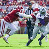 Sophomore runningback Charles Jones rushes for a small gain as Oklahoma players bring him down during the third quarter of the No. 14-ranked Wildcats' 31-30 upset of the No. 11-ranked Sooners October 18, 2014, at Gaylord Family Memorial Stadium in Norman, Oklahoma. (Parker Robb   The Collegian)