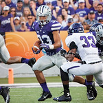 (Photo by Emily DeShazer | The Collegian)  A K-State running back rushes away from defenders on August 30, 2014 at Bill Snyder Family Stadium.
