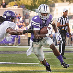 (Photo by Emily DeShazer | The Collegian)  Sophomore wide receiver Deante Burton runs out of the grasp of a Stephen F. Austin defender on August 30, 2014 at Bill Snyder Family Stadium.