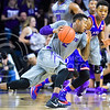 Sophomore guard Marcus Foster dribbles alongside Kansas guard Devonte' Graham looking for an opening in the first half of the Wildcats' 70-63 victory over the #8-ranked Jayhawks in the 281st Sunflower Showdown February 23, 2015, in Bramlage Coliseum. (Parker Robb | The Collegian)