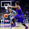 Junior guard Justin Edwards dribbles around Kansas guard Devonte' Graham in the second half of the Wildcats' 70-63 victory over the #8-ranked Jayhawks in the 281st Sunflower Showdown February 23, 2015, in Bramlage Coliseum. (Parker Robb | The Collegian)