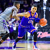 Kansas guard Frank Mason III stiff-arms sophomore guard Jevon Thomas as he dribbles around the ouside of the arc in the first half of the Wildcats' 70-63 victory over the #8-ranked Jayhawks in the 281st Sunflower Showdown February 23, 2015, in Bramlage Coliseum. (Parker Robb | The Collegian)