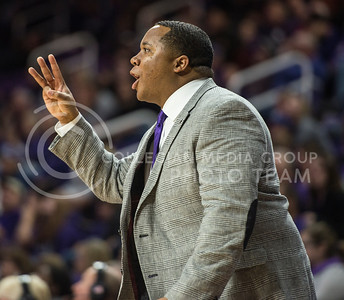 Associate head coach Chris Lowery gives the players a sign on Nov. 17, 2014 at Bramlage Coliseum.  UMKC lost to the Wildcats 83-73.  (Rodney Dimick | The Collegian)