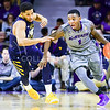 Sophomore guard Jevon Thomas charges past West Virginia guard Gary Browne in the second half of the Wilcats' brutal 59-65 loss to the #17-ranked Mountaineers January 27, 2015, in Bramlage Coliseum. According to the officials, 54 personal fouls were committed between the two teams in the game, and Thomas fouled out of the game in the last minute. (Parker Robb | The Collegian)
