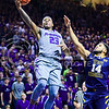 Sophomore guard Nigel Johnson puts a running layup in past West Virginia guard Gary Browne before crashing into the photographers and videographers on the baseline in the second half of the Wildcats' brutal 59-65 loss to the #17-ranked Mountaineers January 27, 2015, in Bramlage Coliseum. (Parker Robb | The Collegian)