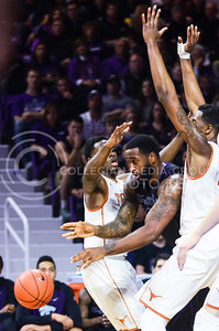 Senior forward Thomas Gipson attempts to squeeze a pass around Texas guard Kendal Yancy (left) and center Prince Ibeh (right) in the second half of the Wildcats' 57-61 shortcoming at the hands of the #25 Longhorns February 7, 2015, in Bramlage Coliseum. (Parker Robb | The Collegian)