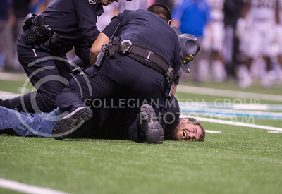 A UCLA fan smiles as he is handcuffed after running onto the field during the 2015 Alamo Bowl game against UCLA on Jan. 2, 2015. (George Walker | The Collegian)