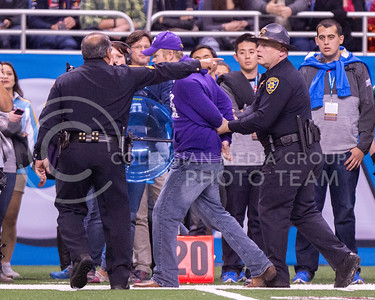Police officers escort the K-State fan that entered the field during the 2015 Alamo Bowl game against UCLA on Jan. 2, 2015. (George Walker | The Collegian)