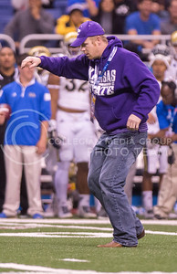 A K-State fan that went onto the field does the K-S-U chant before police officers handcuff him during a timeout of the 2015 Alamo Bowl game against UCLA on Jan. 2, 2015. (George Walker | The Collegian)
