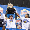 UCLA linebacker Eric Kendricks (right) and Alamo Bowl executives help UCLA head coach Jim Mora lift the extremely-heavy champions' trophy following UCLA's defeat of Kansas State in the Valero Alamo Bowl January 2, 2015, in the Alamodome in San Antonio, Texas. (Parker Robb | The Collegian)
