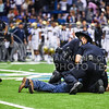 """San Antonio police officers handcuff an unruly fan who ran onto the field during the fourth quarter of No. 11 K-State's 35-40 loss to No. 14 UCLA in the Valero Alamo Bowl January 2, 2015, in the Alamodome in San Antonio, Texas. Soon after this man escorted off the field by police, a K-State fan with a field pass ran into the middle and led fans in the """"K-S-U"""" cheer, and he too was escorted away by police after running to the sidelines and surrendering. (Parker Robb 