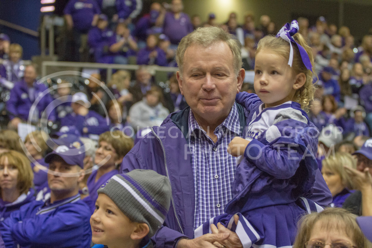 Holding his granchild, a Kansas State Univeristy fan, watches the pep rally taking place in the front. The pep rally was sponsered by the Alumni Association and took place on Jan.1. (Mason Swenson | The Collegian)