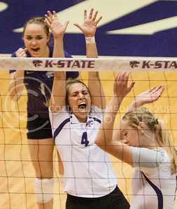 Kiersten Kober, left, Sheridan Zarda and Kylee Zumach celebrate Zumach's kill during the third set Wednesday at Ahearn Fieldhouse. The Wildcats defeated the Iowa State Cyclones in four sets to become 3-1 in conference play. (Emily DeShazer | The Collegian)