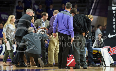 Head coach Jeff Mittie helps others move Haley Texada safely to the nearby stretcher on Jan. 11, 2014 at Bramlage Coliseum.  (Rodney Dimick | The Collegian)