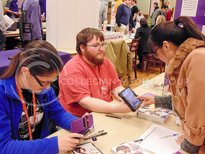 Qian Niu, freshman in the English Learning Program asks current Anime and Manga Society president Ben Dodge, senior in digital art, and Ella Popova, senior in biology questions about their club. This occured at the Wildcat Winter Expo in the Student Union Grand Ballroom on Jan. 28, 2016. (Jessica Robbins | The Collegian)