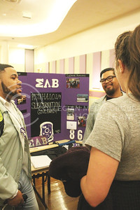 Ty Herbin, junior in secondary education, and Jaylan Padilla, junior in kinesiology, share with Jordan Priddle, assistant director of fraternity and sorority life, what their Sigma Lambda Beta International fraternity participates in and supports in the Union Grand Ballroom at the Wildcat Winter Expo on Jan. 28, 2016.   (Emily Lenk | The Collegian)