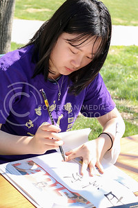 Junye Liu, International Week Game Day worker, translates participant names to Chinese at the International Week Game Day in the Quad on April 4, 2016. (Matthew Zajic | The Collegian)