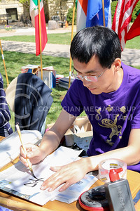Shijun Yan, International Week Game Day worker, translates participant names to Chinese at the International Week Game Day in the Quad on April 4, 2016. (Matthew Zajic | The Collegian)
