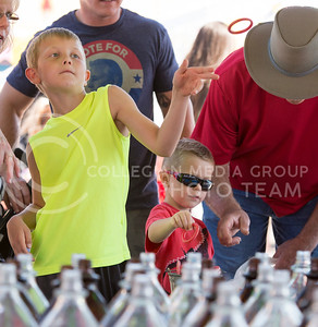 Cody Klocek, 8-year-old from Andover, throws a ring at a bottle in an attempt to win a prize during the Kansas State Fair on Sept. 12, 2015. (George Walker | The Collegian)