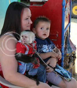 One year old Isaiah Perales is skeptical of the primate he's being told to take his picture with at the Kansas State Fair on Saturday. (Vail Moshiri | The Collegian)