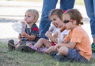 (Left to right) Thomas Bridgeman, 6, Izzie Bridgeman, 4, and Aiden Bridgeman, 6, eat corndogs at the Kansas State Fair on Sept. 12, 2015. (George Walker | The Collegian)